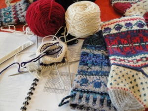 class workbook with sample stockings and a just-started stocking on double pointed knitting needles using white, red and blue yarns.