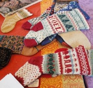 Two colorful Christmas stockings in greens, white and red, knitted with four different patterns, starting at the cuff, and separated by knitted braids. Heels and toes knitted in red. One says Noel with Green fir trees above. The other has a band of holly and a band of people.
