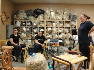 two women seated at spinning wheels listening to woman instructing at front of room. Shelves of raw fleece line the wall behind them. All are smiling.