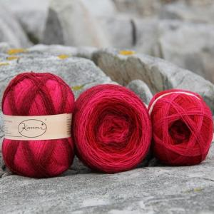 View of three balls of yarn. Shades of red to bright pink in each ball