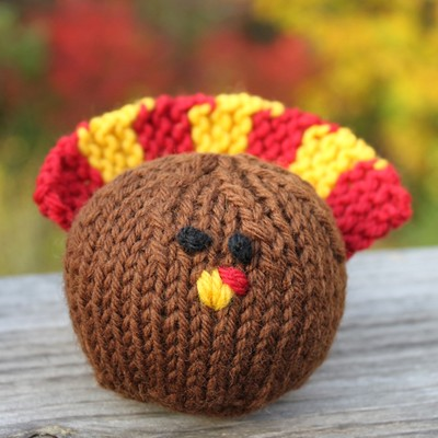 Knitted turkey. Round brown body, yellow beak with red spot. Little black eyes. Red and yellow tail feathers.